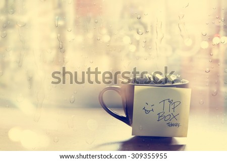 Tip box, coin in the coffee cup in cafe front of mirror and rain water drop, Vintage color and soft concept - stock photo