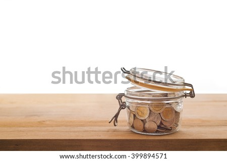 Tip box, coin in the glass jar on wooden white background - stock photo