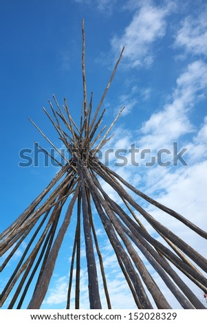 Tipi poles with a sky background - stock photo