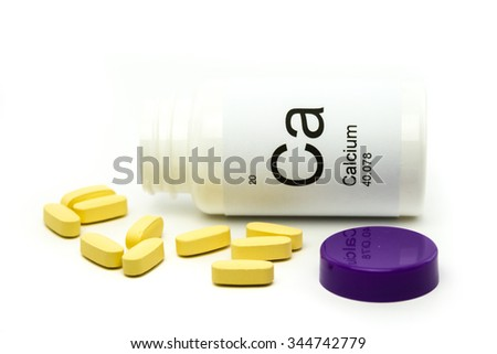 Tipped over bottle of Calcium vitamins - stock photo