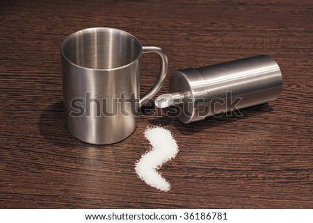 Tipped over sugar dispenser, tea cup and a sugar pile on brown wooden table - stock photo