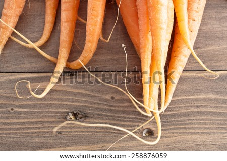 Tips of freshly harvested carrots on a wooden surface - stock photo