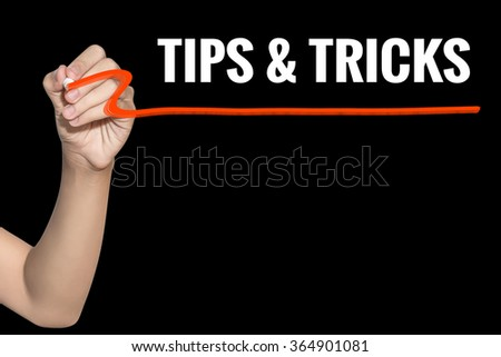 Tips & Tricks word write on black background by woman hand holding highlighter pen - stock photo