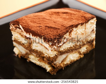 Tiramisu cake in a black plate, close up - stock photo