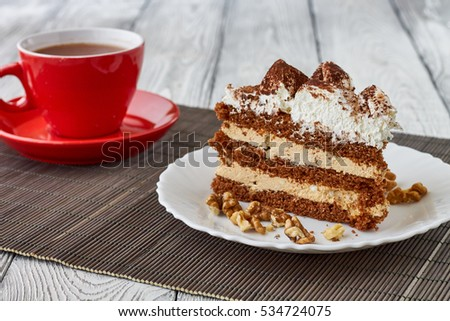 Tiramisu cake with walnuts and coffee on a wooden background