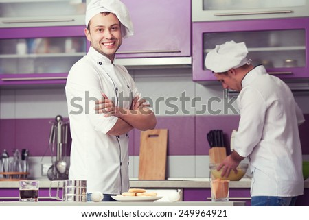 Tiramisu cooking concept. Portrait of two smiling men in cook uniform making italian dessert in modern kitchen. Indoor shot - stock photo