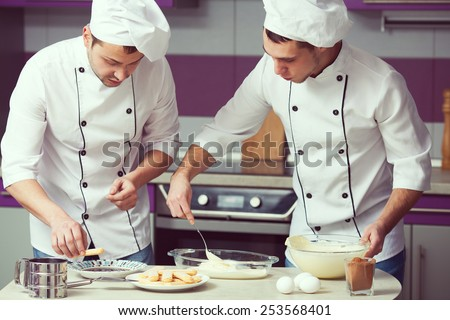 Tiramisu cooking concept. Portrait of two working men in cook uniform making italian dessert in modern kitchen. Indoor shot