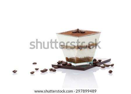 Tiramisu dessert on chocolate bar with coffee beans isolated on white background. Italian sweet dessert concept. - stock photo