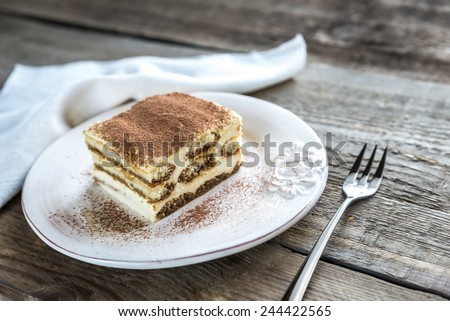 Tiramisu in the plate on the wooden background - stock photo
