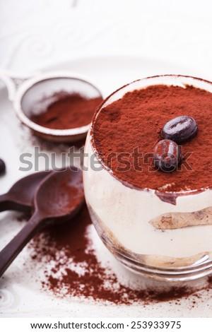 Tiramisu, traditional Italian dessert in a glass,with chocolate spoons.selective focus - stock photo