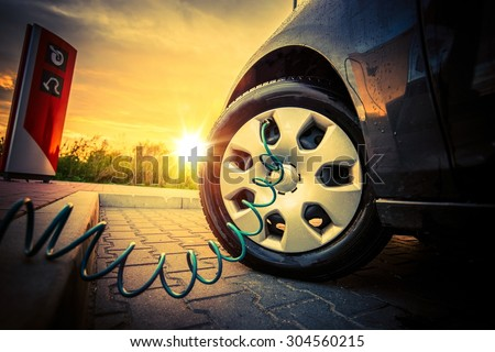 Tire Air Pressure Check at the Check Station During Sunset. Pumping Air into Tire. - stock photo