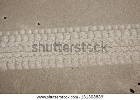 Tire footprint on the beach - stock photo