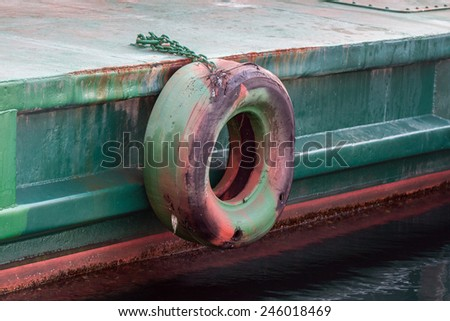 Tire is hanging around the side boat for cushioning. - stock photo
