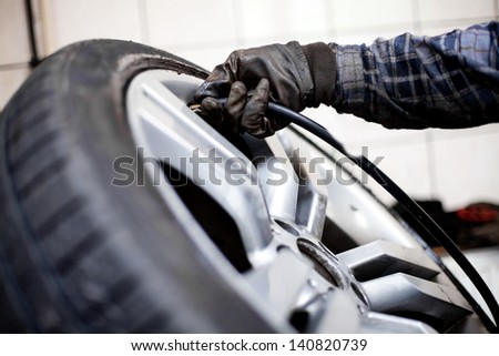 Tire pressure check. Closeup of mechanic inflating tyre with alloy wheel - stock photo