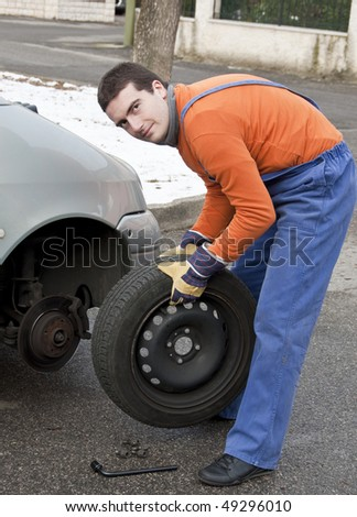 tire repairer changing a car  flat - stock photo
