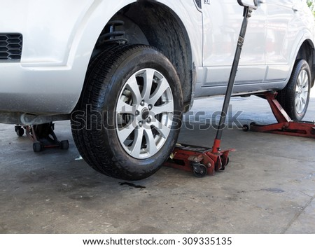 Tire replacement service fitting by hand jack  - stock photo