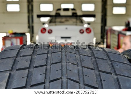 Tire texture closeup with race car parked in garage in the background - stock photo