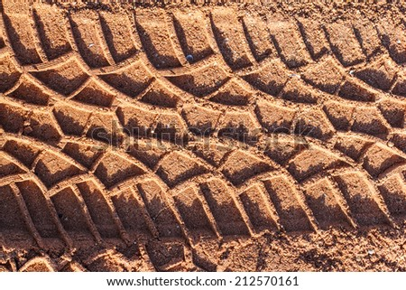 Tire track on muddy road - stock photo