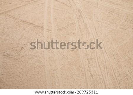 Tire tracks and footprint on the beach - stock photo