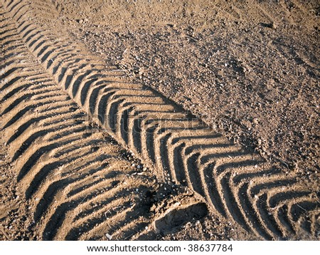 Tire tracks from a heavy vehicle in sand - stock photo