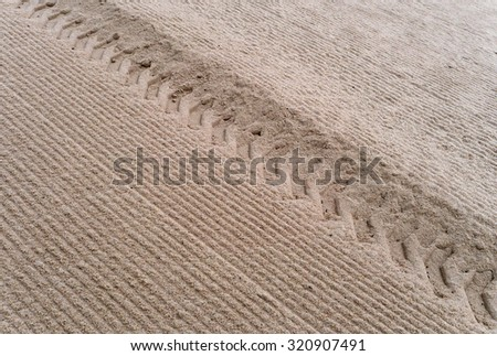 Tire tracks in the sand - stock photo