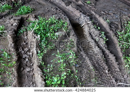 Tire tracks on a muddy dirt road. Traces of the wheel off-road vehicle in the mud after skidding. Dirty rural dirt road after a rain with deep tire tracks - stock photo