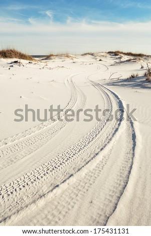 Tire tracks wind through pristine white beach sand dunes to the ocean. - stock photo