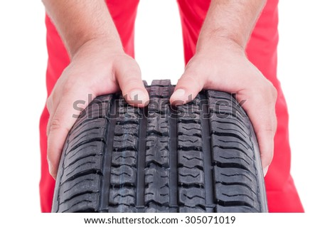 Tire vulcanization services concept with mechanic pushing car wheel - stock photo