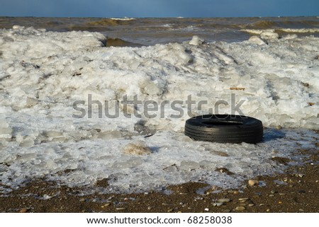 Tire washed up along the frozen shore of Lake Erie - stock photo