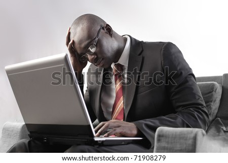Tired african businessman using a laptop - stock photo