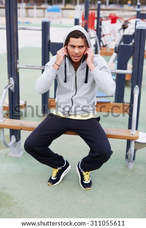 Tired after active physical exercise handsome fit man taking a break while sitting on training apparatus outside, male athlete having a rest after workout while he listening to music with headphones - stock photo