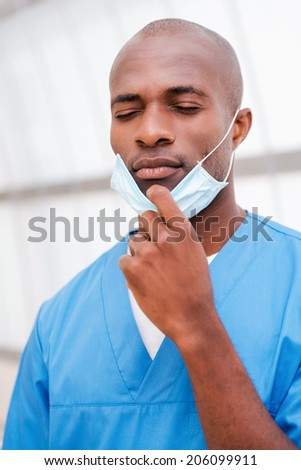 Tired after long surgery. Portrait of tired young African doctor in blue uniform taking of his surgical mask and keeping eyes closed - stock photo