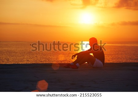 Tired after morning jogging athletic runner resting on the beach, male runner taking break after training outdoors, runner resting on colorful sunrise background, healthy lifestyle concept