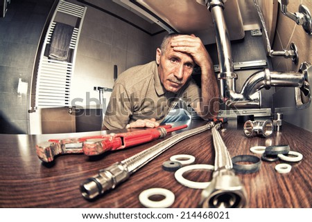 tired an worry plumber at work - stock photo