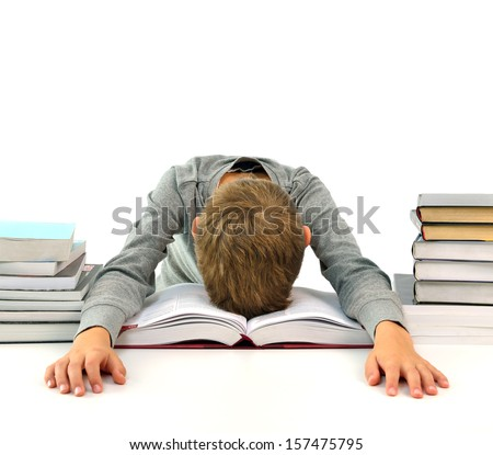 Tired and bored boy sleeping among the books - stock photo