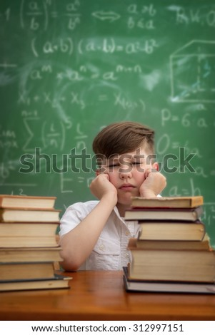 tired and bored schoolboy sitting at a table with books, emotion expression