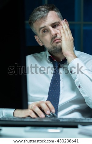 Tired and overworked businessman sitting beside desk at office at night - stock photo