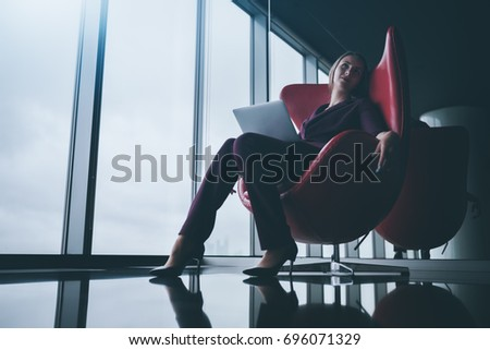 Tired and relaxed boss woman with laptop is sprawling in bent red armchair in office chill out area and dreamy looking up, with copy space place for logo, your text or other advertising