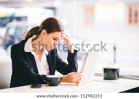 Tired and stressed businesswoman reading emails in cafe - stock photo