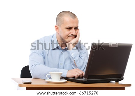 Tired and stressed young businessman working at his computer - stock photo