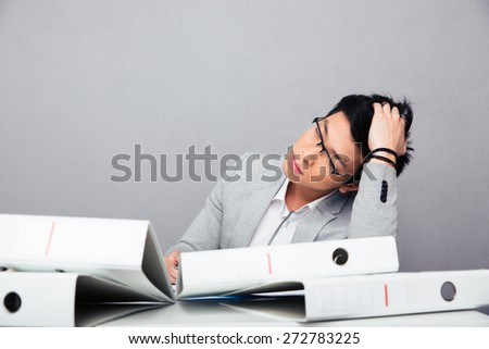 Tired asian businessman sleeping at the table with folders in office - stock photo