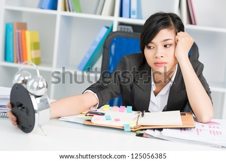 Tired asian businesswoman looking at alarm - stock photo