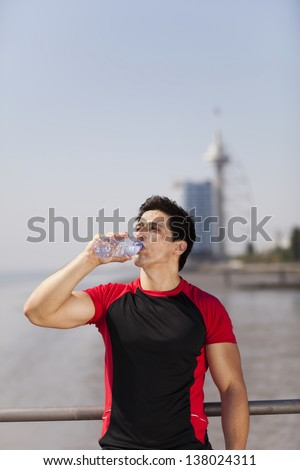 Tired athlete refreshing him self with fresh water - stock photo
