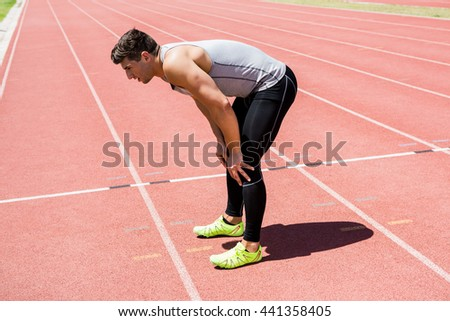 Tired athlete standing on running track on a sunny day
