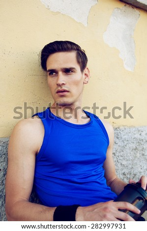 Tired athletic man resting after work out with his protein shake - stock photo