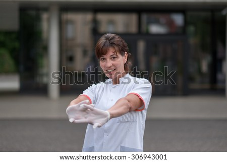 Tired attractive female doctor or nurse standing outdoors in front of the clinic stretching her arms and flexing her fingers as she tries to relax and unwind - stock photo