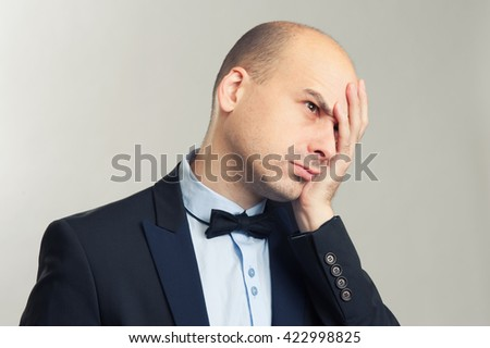 tired bald man. Isolated over gray background. - stock photo