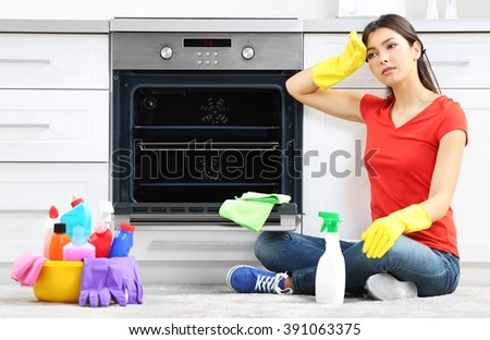 Tired beautiful woman in protective gloves after cleaning - stock photo