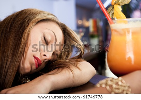 Tired beautiful women with cocktail in hand - stock photo