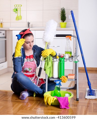 Tired beautiful young woman sitting on the kitchen floor with cleaning supplies on ladder and feeling bored - stock photo